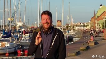 A portrait of historian Michael Busch, smiling at a harbor.