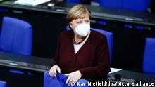 Merkel, wearing a mask, in the Bundestag before her speech