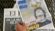 25.11.2020, Cali, Kolumbien, A worker holds newspapers with photos of late Argentinian football legend Diego Maradona on the front page, early on November 26, 2020, in Cali, Colombia at the El Pais de Cali newspaper printing facility. - Millions of fans paid tribute and Argentina was plunged into mourning on November 25 as Maradona, one of the greatest footballers of all time, died aged 60 after years of drug and alcohol problems. (Photo by Luis ROBAYO / AFP) (Photo by LUIS ROBAYO/AFP via Getty Images)