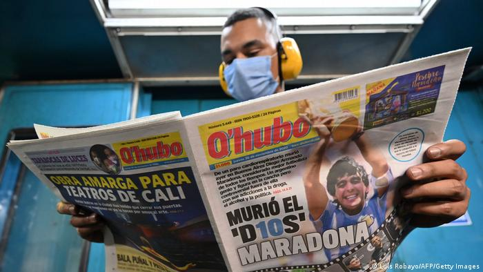 Foto simbólica de una persona leyendo un ejemplar del periódico Q'Hubo