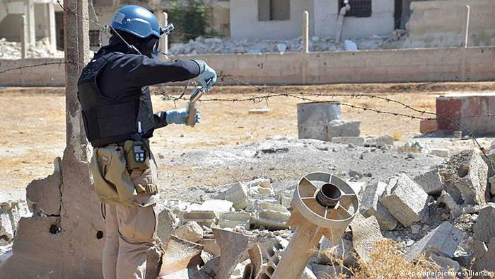 A UN weapons inspector collects samples during the team's investigations near the attack site