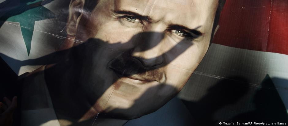 Shadows of Syrians are reflected on a giant poster showing President Bashar Assad