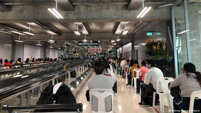 Passengers wait distanced at the airport in Bangkok