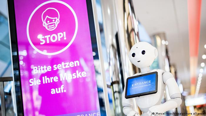 A sign in German reads: 'Please put on your mask'
