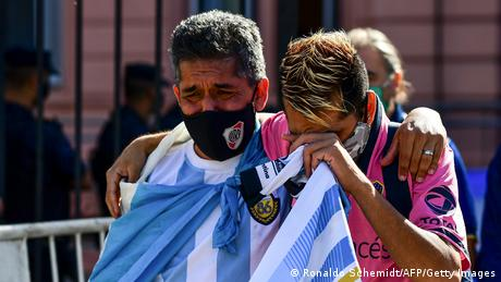 Fans mourn outside the Casa Rosada government house as they wait to pay tribute to Argentinian late football legend Diego Armando Maradona in Buenos Aires