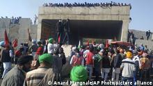 Farmers stand on an under construction flyover, set up by security officers to prevent their protest march to Delhi