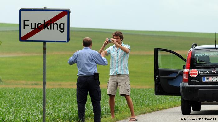 گردشگران در حال عکاسی با تابلوی ورودی و خروجی روستا