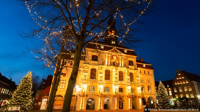 The town hall in Lüneburg with decorated, lit Christmas trees and fairy lights