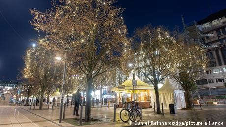Germany, trees with festive lights and some Christmas market stalls in Hamburg