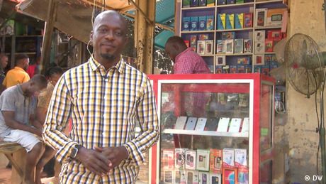 Nneota Egbe, Ecp Africa presenter, in front of a small market stall selling mobile phones