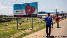 People pass by an AIDS Healthcare Foundation awareness billboard in Maputsoe, Lesotho, on January 31, 2020. (Photo by Michele Spatari / AFP)