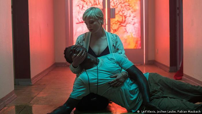 The asylum seeker Francis, played by Welket Bungué, and Jella Haase, embrace in a scene from Berlin Alexanderplatz