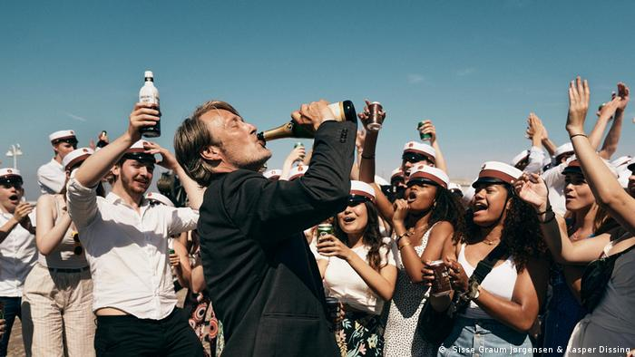 A still from the film Another Round in which the main actor chugs alcohol surrounded by cheering students.