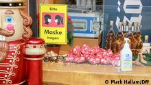 Close-up photo of the bar of a stall in Cologne selling mulled wine, showing a bottle of hand sanitizer provided for customers, and a sign asking that they wear face masks when buying their drinks or snacks. November 27, 2020.