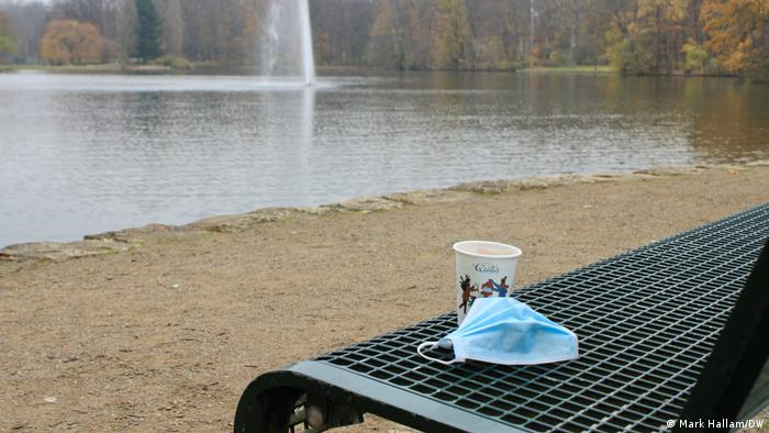 A cup of mulled wine placed on a bench, next to a protective face mask, in Lindenthal in Cologne. November 27, 2020.