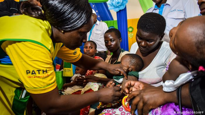 A health worker inoculates a toddler sitting on his mother's lap against malaria
