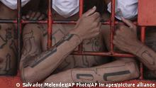 Salvadoran 18th Street gang members look out from behind bars during a media tour of the prison in Quezaltepeque, El Salvador, Friday, Sept. 4, 2020. (AP Photo/Salvador Melendez)  