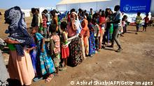 Ethiopian refugees from Tigray region stand in a line for food
