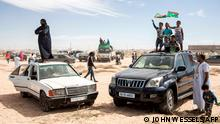 People gather around and on cars to watch the military parade and celebrations for the sixtieth anniversary of Independence for Mauritania in Nouakchott on November 28, 2020. (Photo by JOHN WESSELS / AFP)