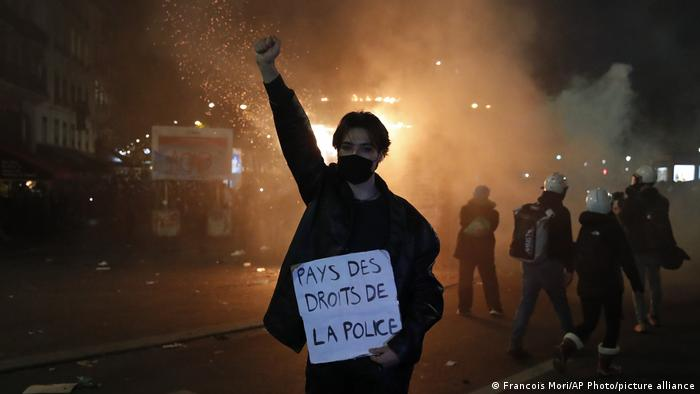 A protester holds a poster reading Land of Human Rights, Police during a demonstration against a security law in Paris, France