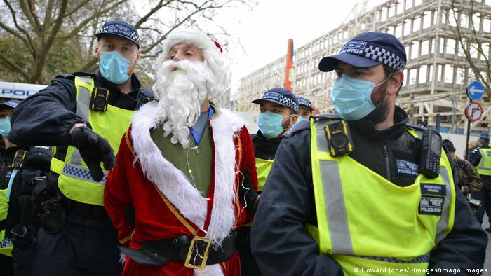 An anti-COVID-19 lockdown protester dressed as Father Christmas is arrested by police during a demonstration in London