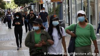 Прохожие в масках на одной из улиц Никосии