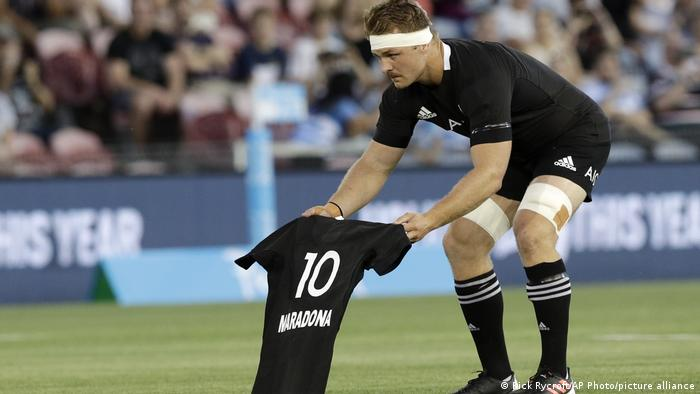 New Zealand captain Sam Cane laying a shirt in the middle of the pitch with Maradona's name on it