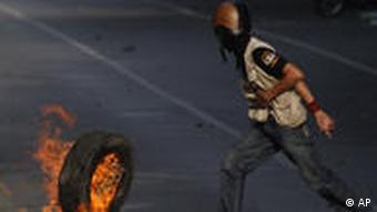 Ein Demonstrant rollt einen brennenden Reifen in Richtung Soldaten (Foto AP)