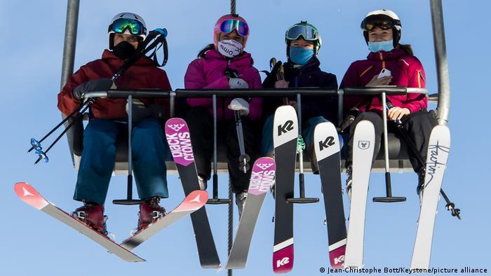 Лыжники в масках на подъемнике в Швейцарии