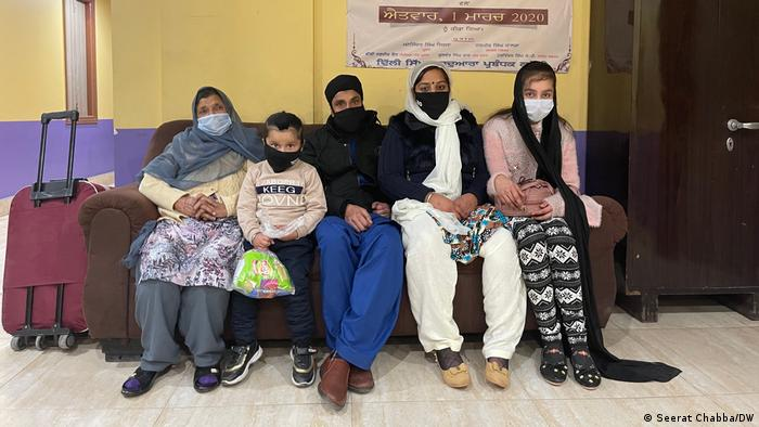 A family sits on a sofa in a Sikh temple