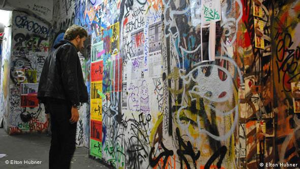 A man stands in front of a colorful wall inside of Tacheles in Berlin