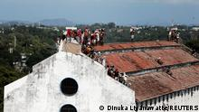 Inmates protest on the top of a prison building demanding to speed up their judicial process and that they be granted bail, after the number of the coronavirus disease (COVID-19) cases increased in prisons in the country, in Colombo, Sri Lanka November 18, 2020. REUTERS/Dinuka Liyanawatte