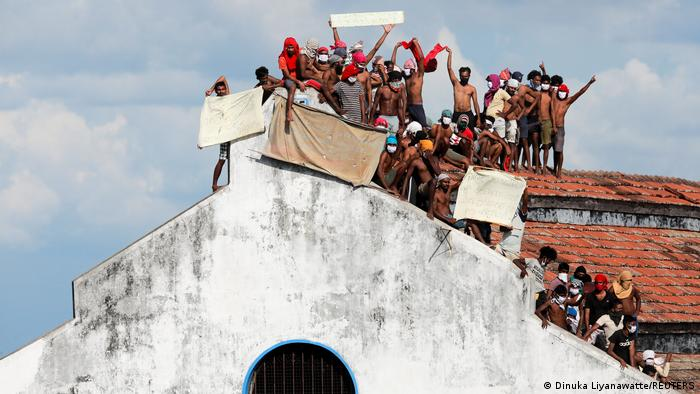 Inmates protest on the top of a prison building in Colombo