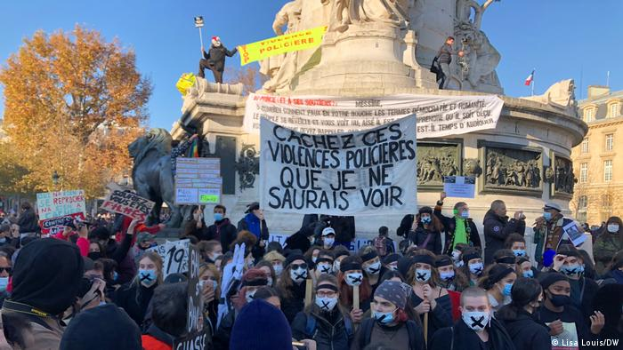 Protesters in the Place de la Republique hold up banners