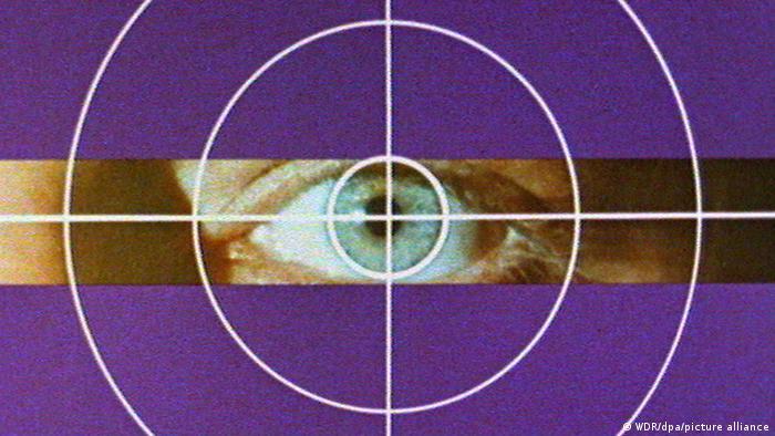 Ein Auge blickt durch ein Fadenkreuz