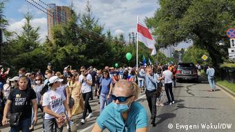 Юноша несет бело-красно-белый флаг на демонстрации в Хабаровске