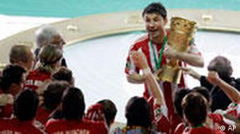 Munich's captain Mark van Bommel holds the cup during the winning ceremony for German Soccer Cup final in Berlin, Germany, Saturday, May 15, 2010