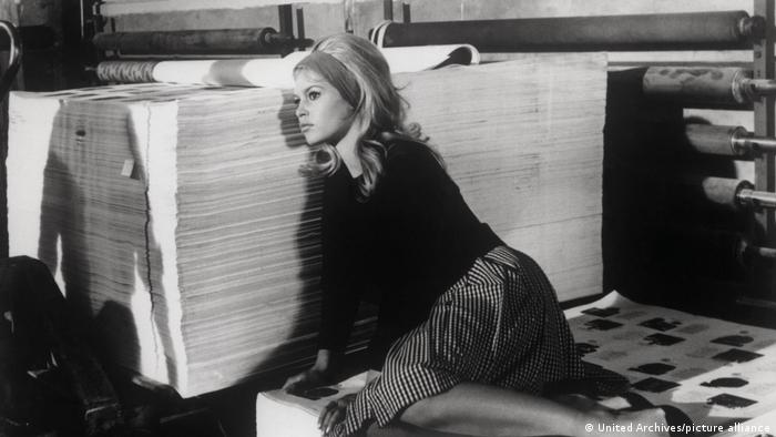 Film still from Contempt, Brigitte Bardot sits on the floor and leans against a large pile of sheets of paper.