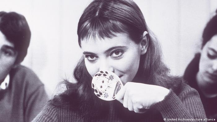 Film still Band of Outsiders , actress Anna Karina holds a hairbrush to her nose and smiles .