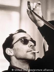 Jean-Luc Godard studying a strip of film while smoking a cigarette