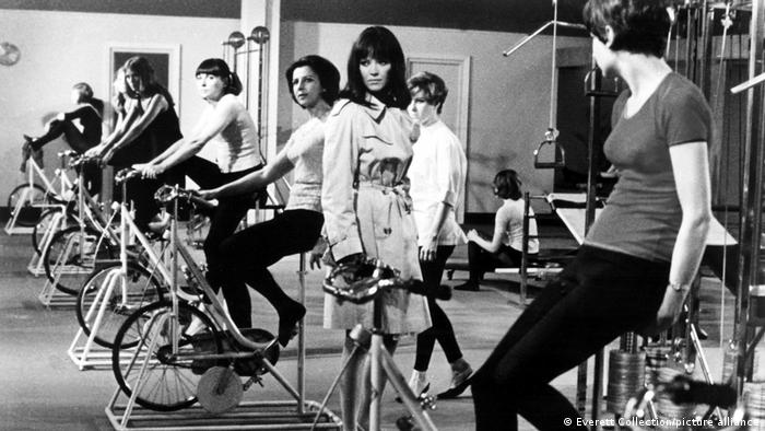 Film still Made in U.S.A. A woman in a raincoat stands between women women on bikes in a fitness studio