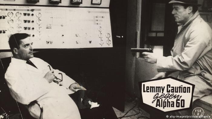 Filmszene: Privatdetektiv Lemmy Caution bedroht mit einer Pistole einen Mann im weißen Kittel.