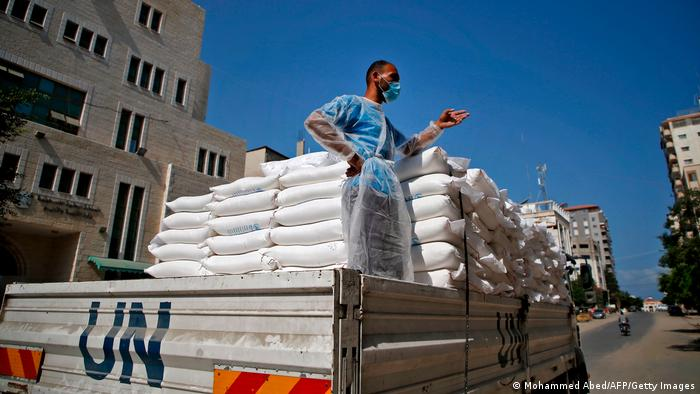 Masked Palestinian relief work stands in the back of a UN truck delivering food.