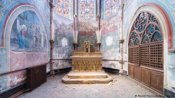 Interior de una capilla con un altar que se desmorona y frescos deteriorados en las paredes.