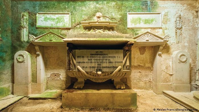 Interior de una cripta con las paredes llenas de moho.