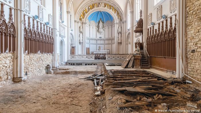 Interior de una capilla con el suelo levantado y muy deteriorado.