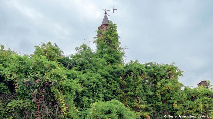 Exterior de una iglesia, cubierta por los árboles.