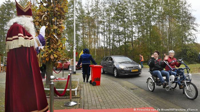 Fahrräder und Autos fahren am winkenden Nikolaus vorbei, Vorden, Niederlande (ANP Piroschka van de Wouw)