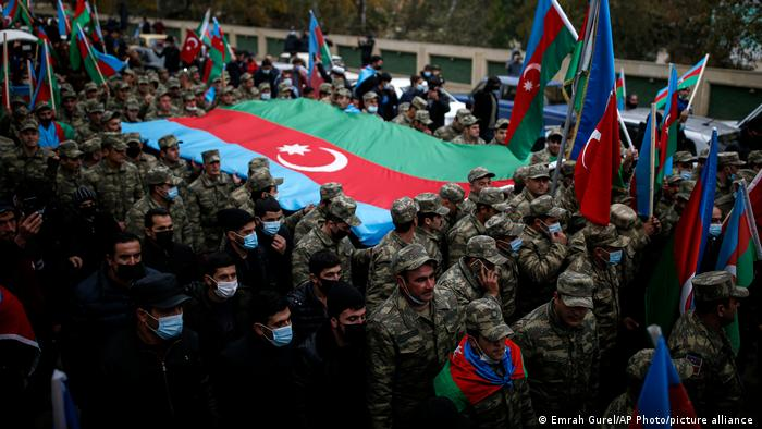 Azerbaijani soldiers carry a huge national flag through Lachin