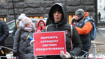 Одна из участниц акции протеста с плакатом в поддержку упрощенной системы налогообложения